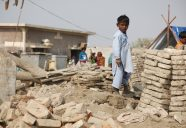 A child stands amongst the remains of buildings destroyed by the
