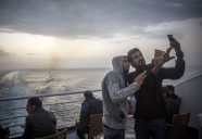 Refugees take photographs aboard a ferry from the northeastern Greek island of Lesbos to the Athens' port of Piraeus, Thursday, Sept. 10, 2015.  The social media-savvy among the migrants are constantly on their phones and they line up outside the offices of mobile providers to buy Greek numbers that allow data and roaming elsewhere in Europe to access social media and communicate with others.   (AP Photo/Santi Palacios)