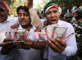 epa05636449 Indian Youth Congress activists show replicas of old Indian Rupee notes during a protest against the Rupee note change in New Delhi, India, 18 November 2016. Indian Bank officials started leaving an ink mark on fingers of people who have exchanged their discontinued Rupee notes for new ones. Indian Prime Minister Narendra Modi announced the elimination of the 500 and 1,000 rupee bills (7.37 and 14.73 US dollars, respectively), hours before the measure took effect at midnight 08 November, for the purpose of fighting against 'black money' (hidden assets) and corruption in the country. The decision sparked some protests, while storekeepers complained about dwindling sales because many citizens lack the cash to buy the most basic products, as lines get longer at ATMs and banks.  EPA/RAJAT GUPTA