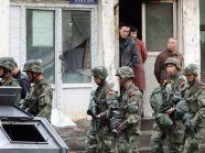 URUMQI, China - Armed police patrol an area where blasts occurred in Urumqi, China's Xinjiang Uyghur Autonomous Region, on May 22, 2014, with broken window glass visible in the background. The blasts killed 31 people and injured 94 others, according to local authorities. (Kyodo)