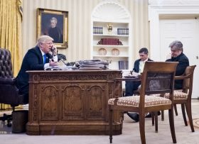 epa05758036 National Security Advisor Michael Flynn (C)  and Senior Counselor to the President Steve Bannon (R), sit nearby as US President Donald J. Trump (L) speaks on the phone with Prime Minister of Australia, Malcolm Turnbull in the Oval Office in Washington, DC, USA, 28 January 2017. The call was one of five calls with foreign leaders scheduled for 28 January.  EPA/PETE MAROVICH / POOL
