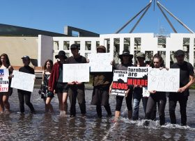 "Members of Whistleblowers Activists and Citizens Alliance protest outside Parliament House in Canberra, Thursday, Dec. 1, 2016. Two members from the group, who disrupted Question Time on Wednesday, have scaled the building's front wall, unfurling a banner which reads ""Close the bloody camps now"". A dozen others have waded out into a pond in the complex's forecourt, holding placards with slogans such as ""Justice for refugees"". (AAP Image/Lukas Coch) NO ARCHIVING"