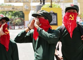 Filipino activists use cloth printed with the hammer and sickle symbol to cover their faces as they shout slogans during a rally near the Malacanang presidential palace in Manila, Philippines, Monday, Aug. 22, 2016. Philippine President Rodrigo Duterte recently reimposed an indefinite cease-fire after communist guerrillas declared their own truce as both sides resume talks aimed at ending one of Asia's longest-running rebellions. (AP Photo/Aaron Favila)