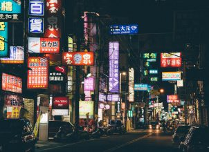 Nighttime street filled with neon signs in Chinese