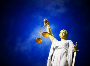 Statue of justice holding measuring scales and sword