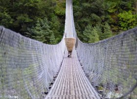 Man walking across bridge in Nepal